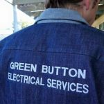 green button electrical services logo on back of shirt